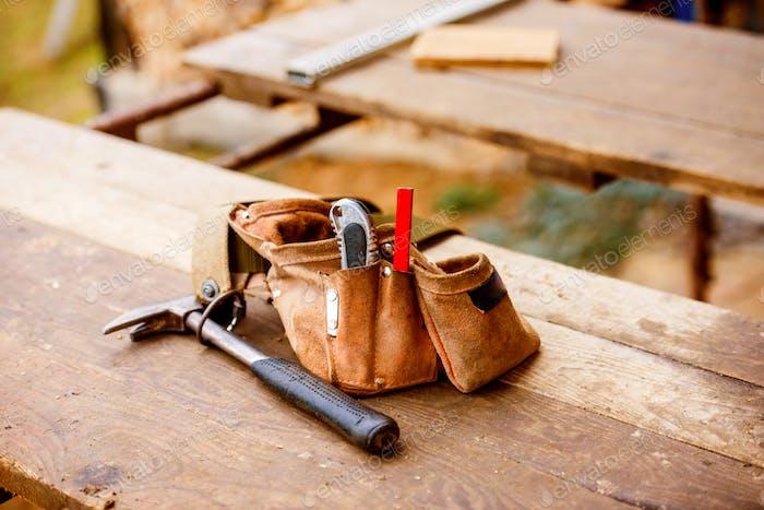 Tischlertasche mit Gürtel voller Werkzeuge, Holztisch