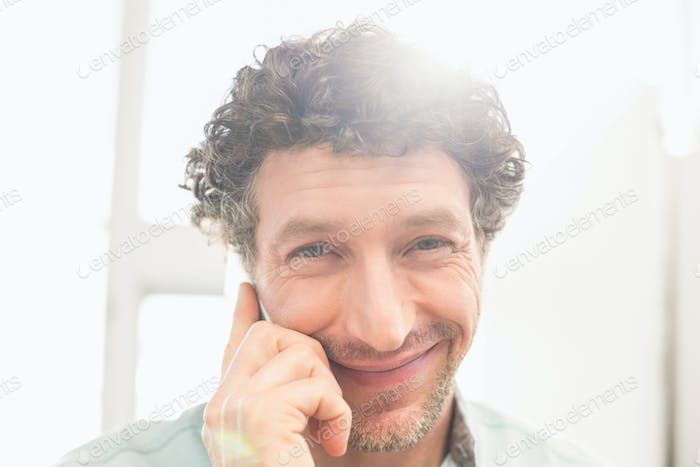 Smiling casual businessman standing and posing in his office