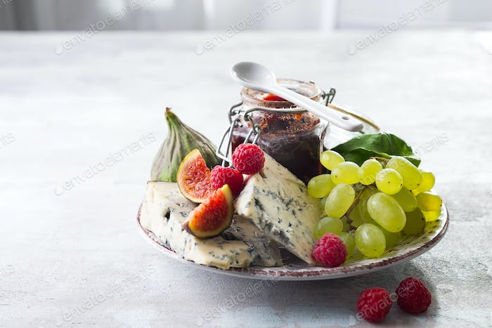 delicacy blue cheeses, fruit and jam in jar on white stone background, copy space