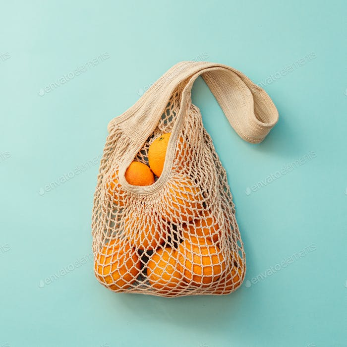 Netzbeutel mit Früchten auf blauem Hintergrund.Zero Abfall