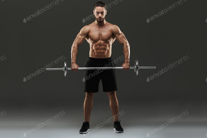 Full length portrait of a concentrated muscular bodybuilder