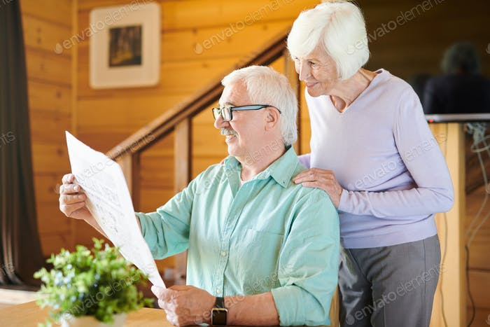 Happy mature man and his wife reading latest news