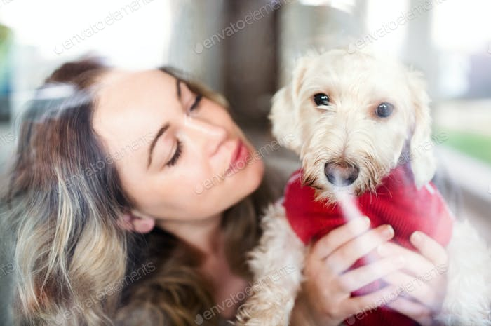 Young woman relaxing indoors at home with pet dog. Shot through glass
