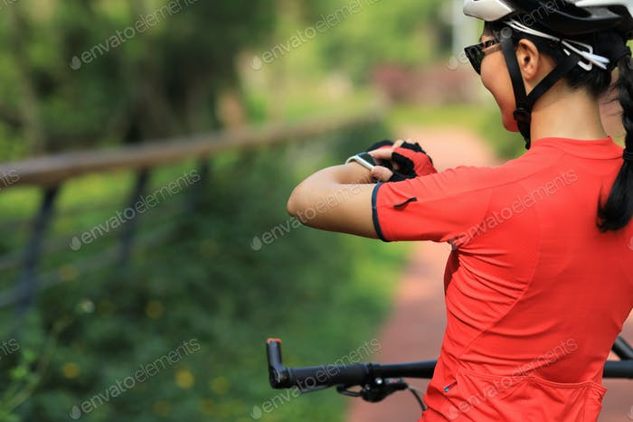 Woman biker looking at her smartwatch outdoors