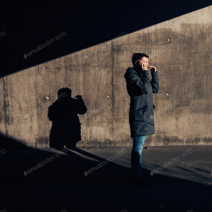 Serious authentic woman talking on mobile phone on the street