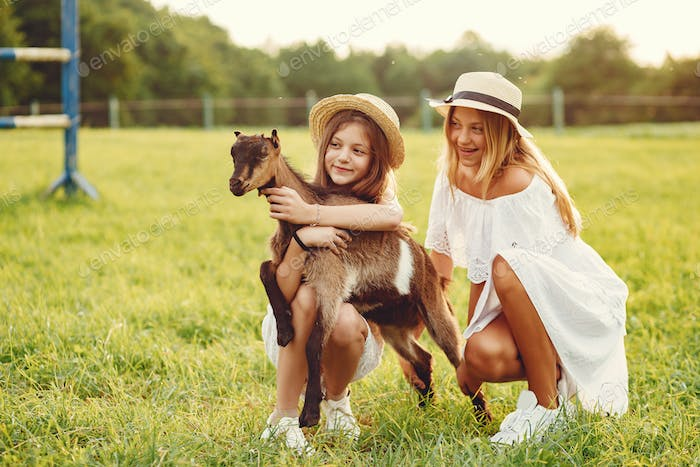 Thumbnail for Two cute girls in a field with a goats