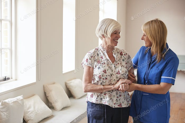 Senior woman comforted by nurse at retirement home