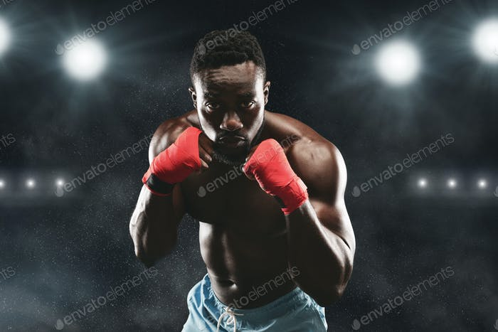Young fighter in boxing stance staying on stadium arena