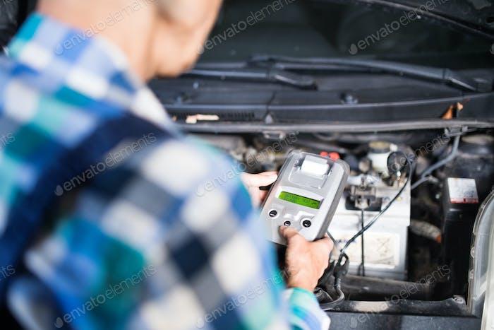 Führende Mechanikerin, die ein Auto in einer Garage repariert.