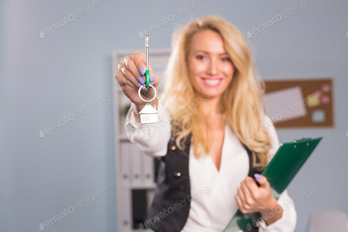 Property concept - Young real estate agent holding keys