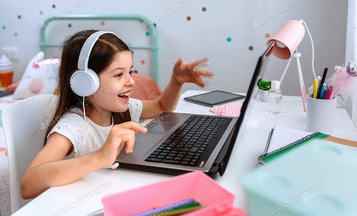 Девушка учится из дома с ноутбуком