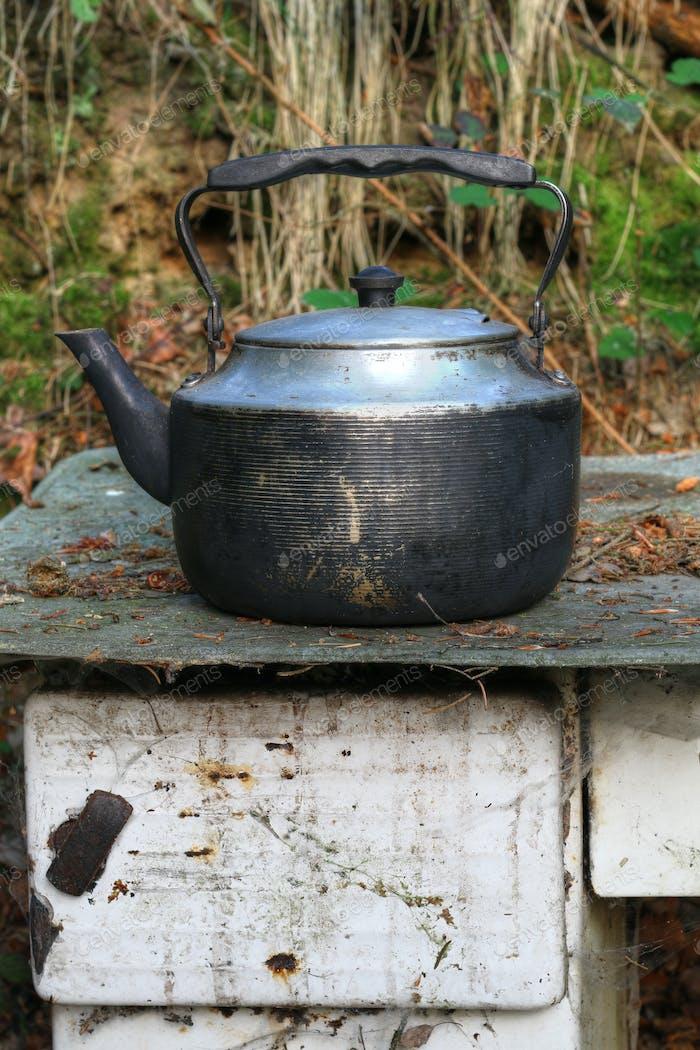 Worn teapot on old stove