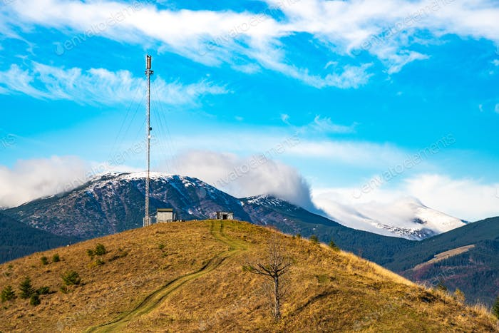 Telecommunication tower against the backdrop of an awesomely beautiful sky with blurry snow-white