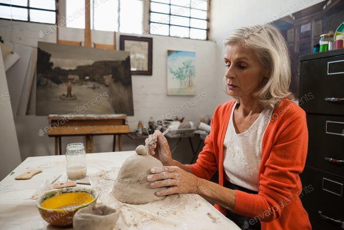 Mid-section of senior woman shaping a clay