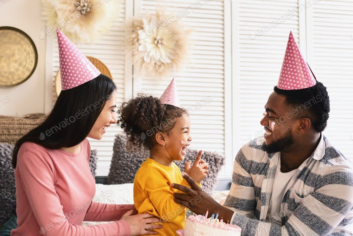 African american father, european mother and daughter smearing with cake