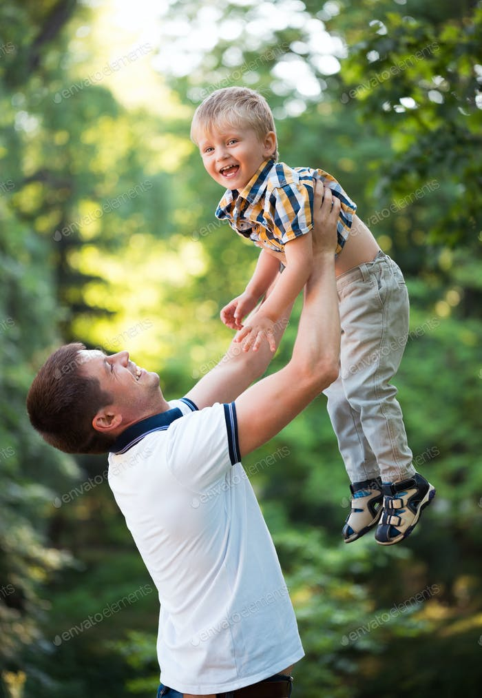 Father and his baby son having fun in the park outdoor