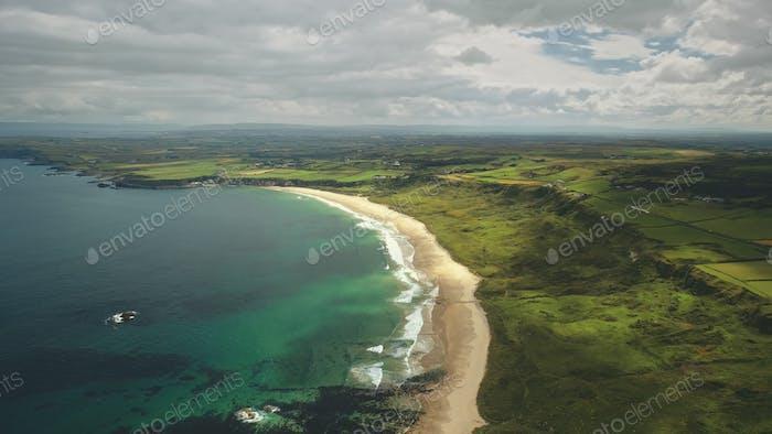 Aerial view sandy coastline, green grass meadows. Waves crashing out of shore Atlantic ocean bay