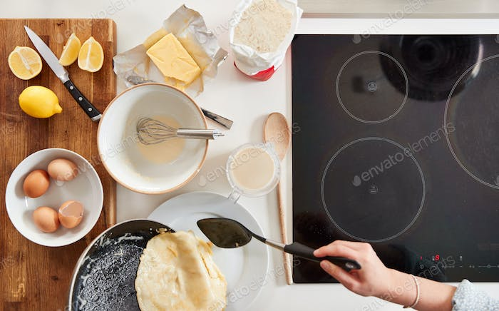 Overhead Shot Of Woman In Kitchen Serving Pancakes Or Crepes For Pancake Day