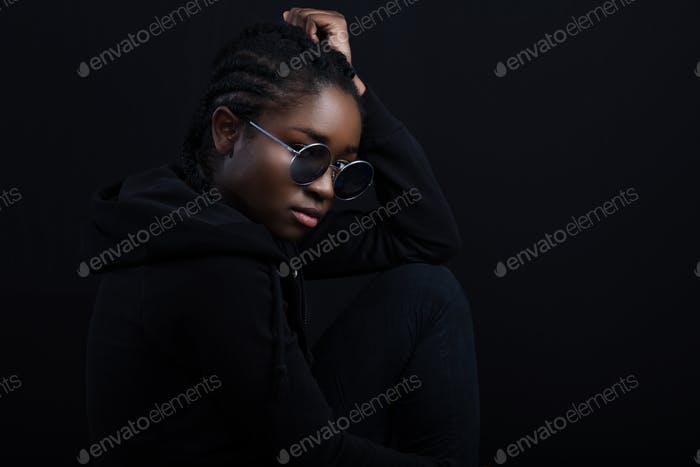 Cool african woman sitting with dark skin wearing round sunglasses