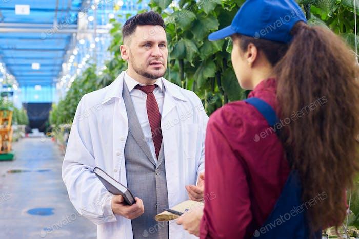 Handsome Scientist Talking to Worker in Greenhouse