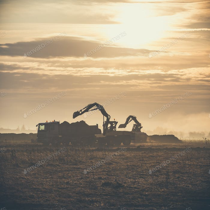 Excavator working on construction site, loading dump track.