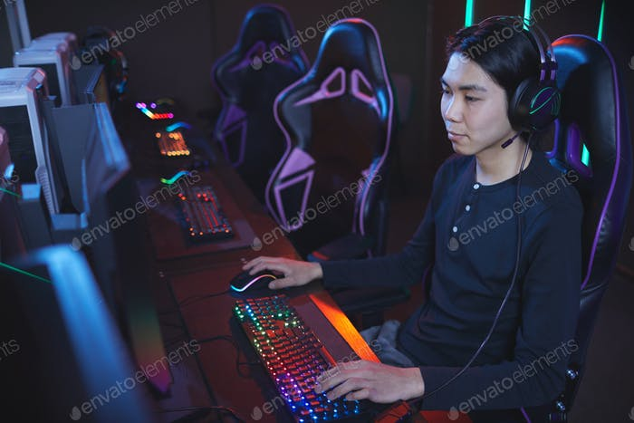 Asian Man Playing Video Games in Computer Club
