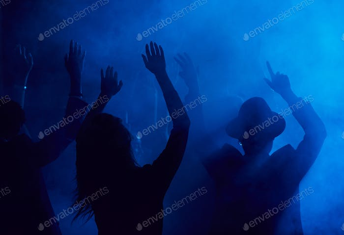 Dancing People in Smoky Nightclub