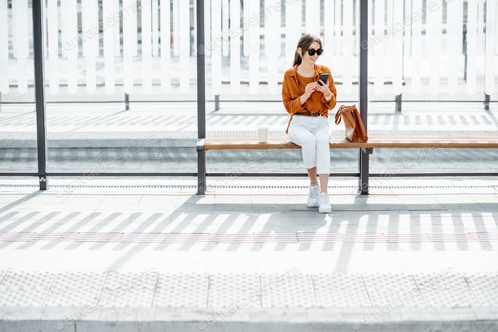 Mujer en la parada de transporte público
