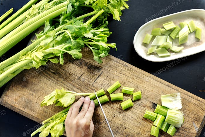 Aerial view of hands with knife cutting celery on wooden cut boa