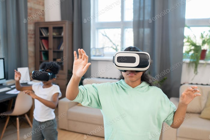 Adorable mixed-race siblings in vr headsets watching video on virtual display