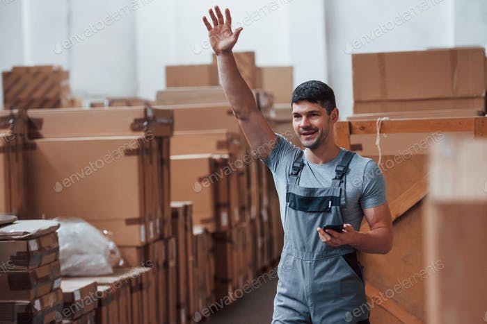Young storage worker in uniform with phone stands and raised hand up