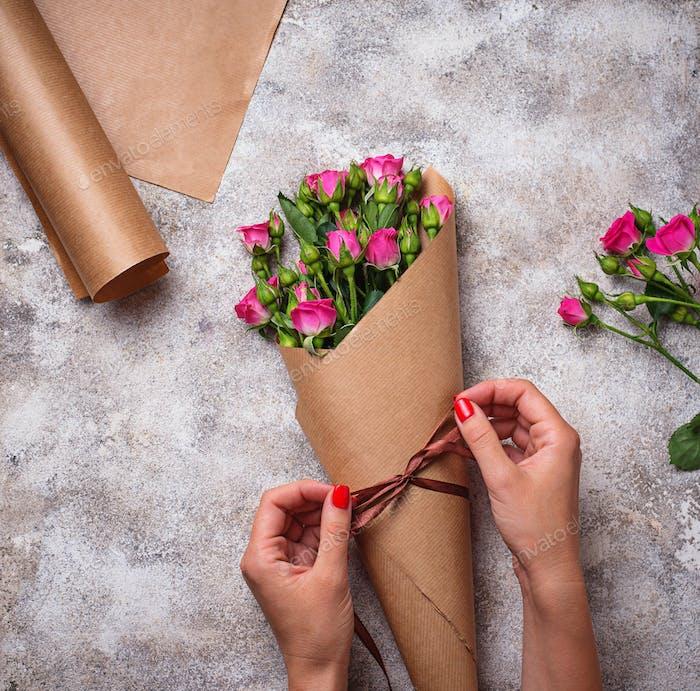 Frauen Hände wickeln einen Blumenstrauß Rosen in Papier
