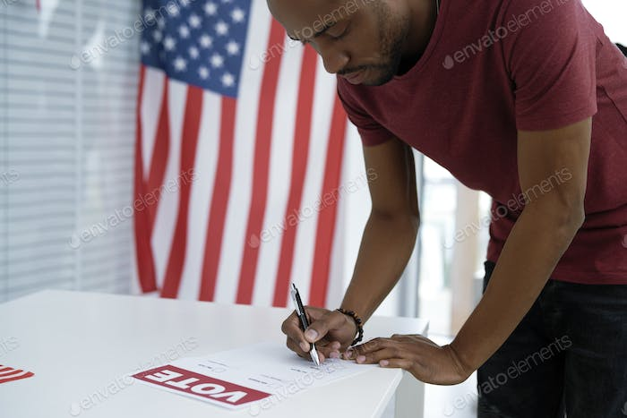 Black man voting in election ballot place