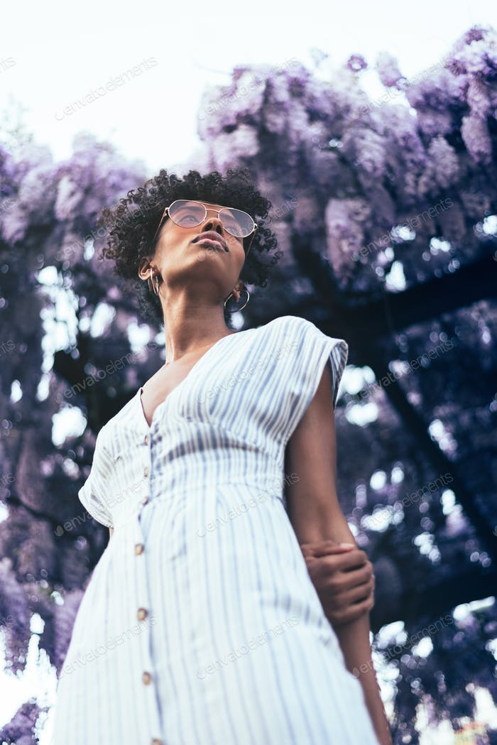 Happy young black woman surrounded by flowers