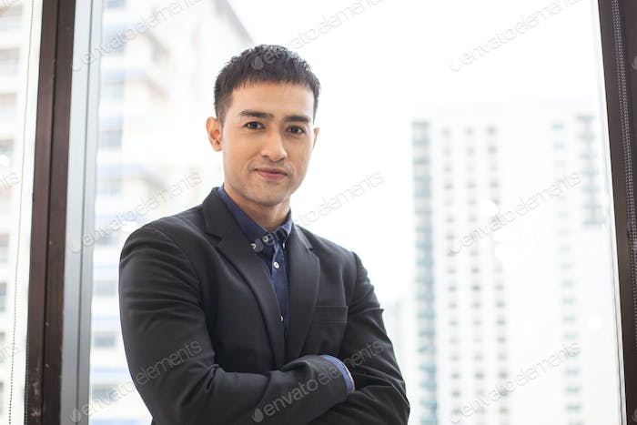 Portrait of confident Asian businessman standing in arms crossed at the office