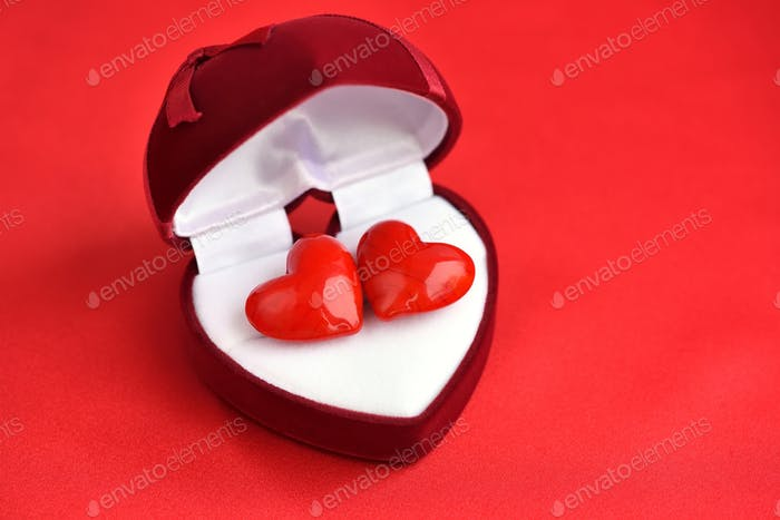 Two decorative hearts are in heart-shaped gift box on red backgr