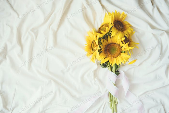 Candid authentic Yellow sunflowers bouquet on fabric white background. Background with bouquet of