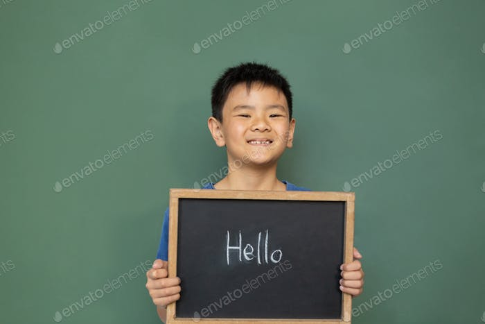 Smiling schoolboy standing and holding a hello slate in a classroom