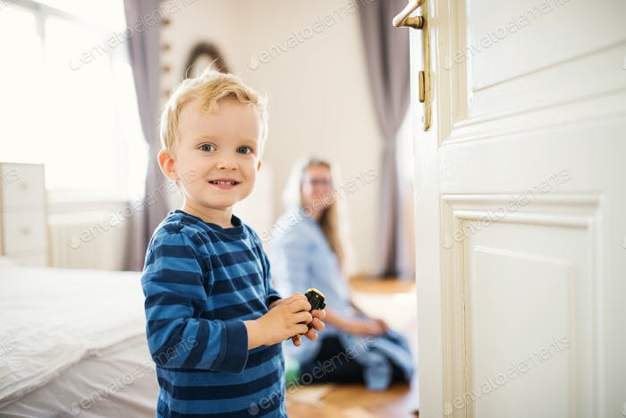 A toddler boy with young mother in the background inside in a bedroom.