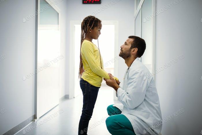 Doktor mit einem traurigen kleinen Mädchen im Krankenhaus. Arzt tröstend Kind