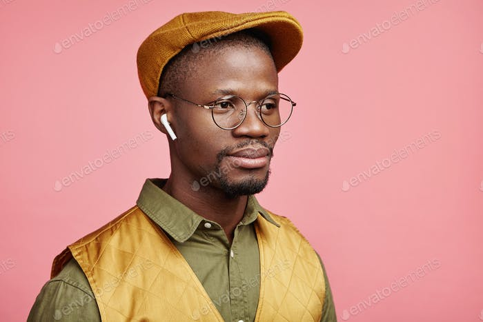 Portrait of fashionable trendy looking middle aged African American male looks into distanse, listen
