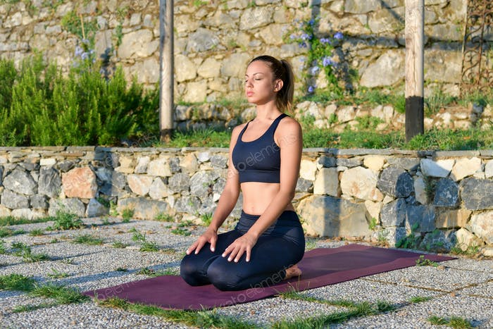 Young woman practicing yoga meditating