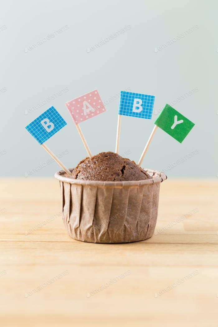 Schokoladenmuffins mit kleiner Flagge eines Wortes Baby