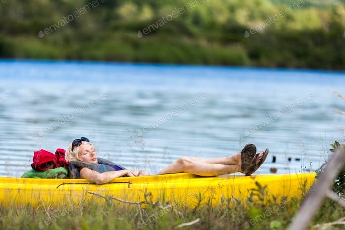 Tired Woman Sleeping in a Kayak