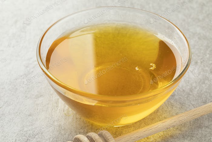Glass bowl with honey and a dipper