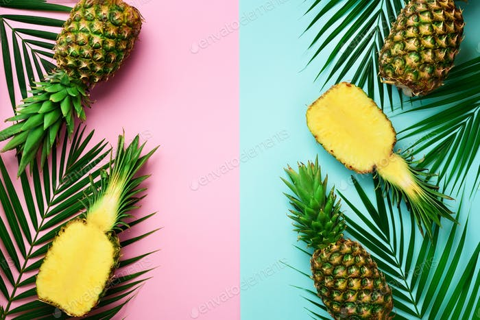 Pineapples, palm leaves on pastel colorful pink and turquoise background with copy space. Creative