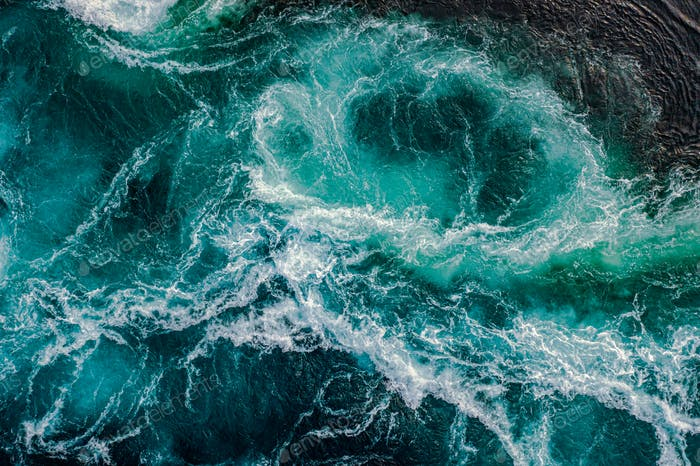 Waves of water of the river and the sea meet each other during h