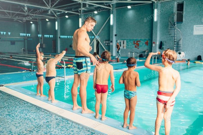 Instructor with children stands near water