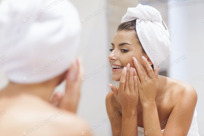 Woman removing pimple from her face