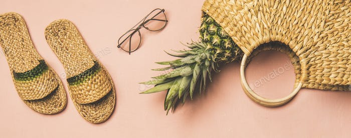 Summer apparel items and pinapple over pink background, wide composition